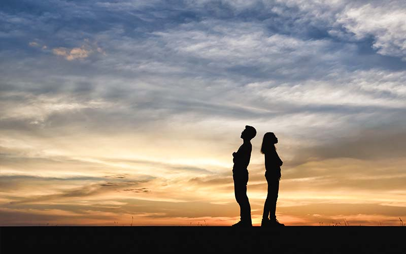 couple in dispute silhouetted on background