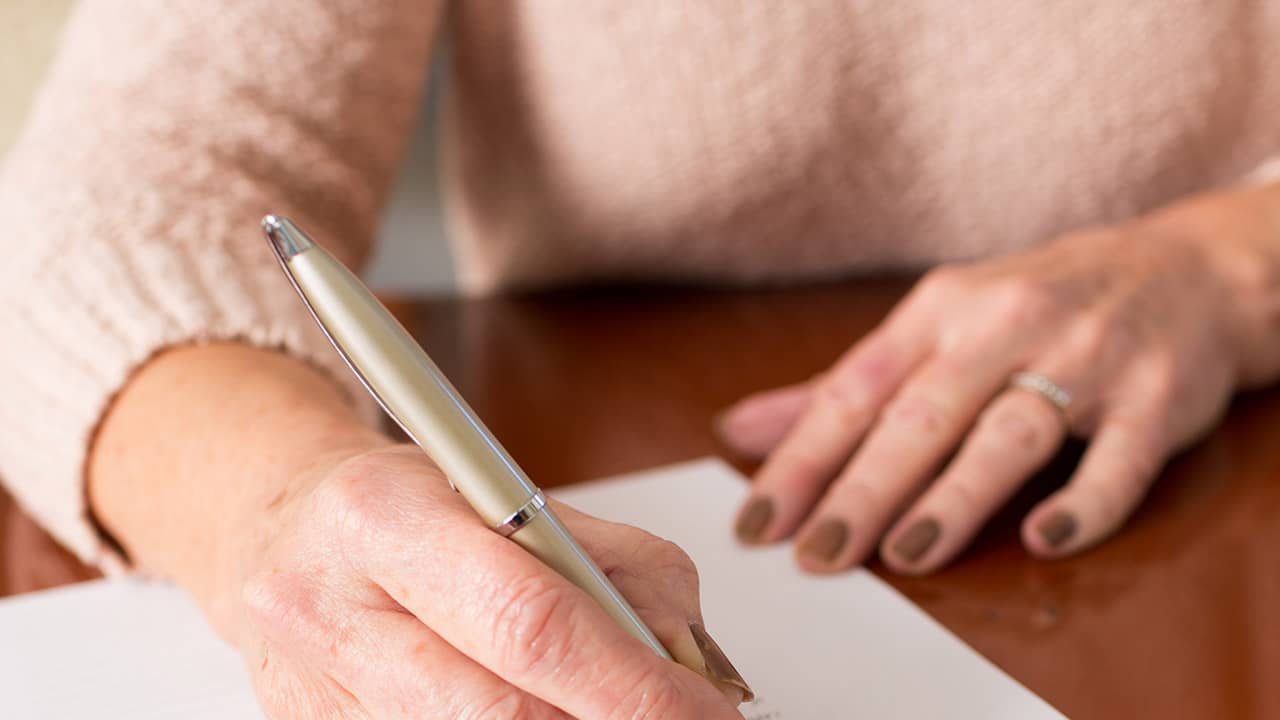 woman signing will papers