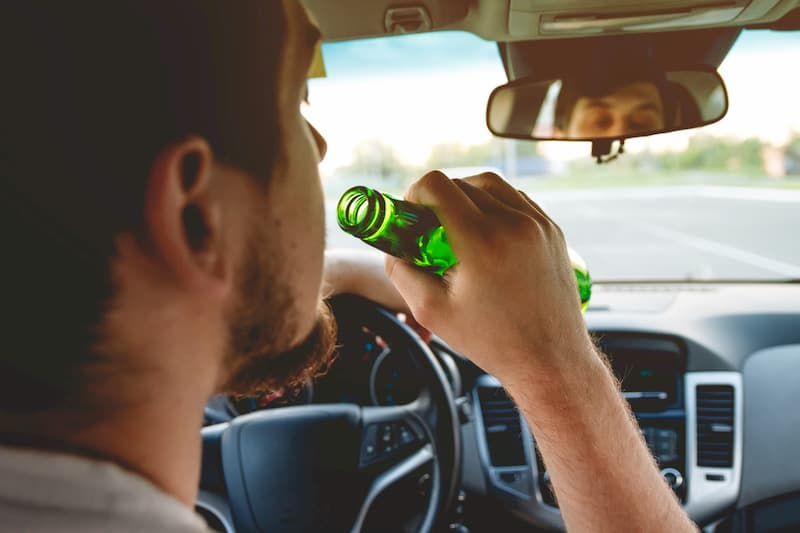 young man drinking and driving